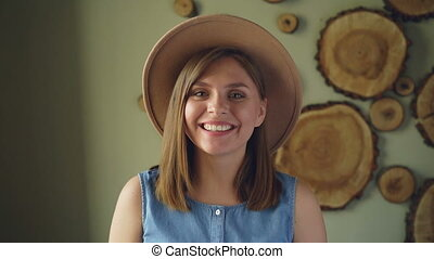Slow motion of pretty blond girl in trendy hat and denim top...