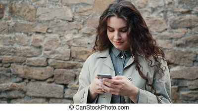 Slow motion of pretty girl using smartphone in street...