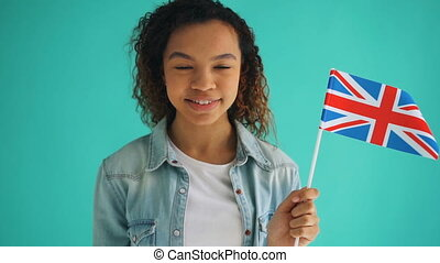 Slow motion of pretty mixed race woman holding flag of...