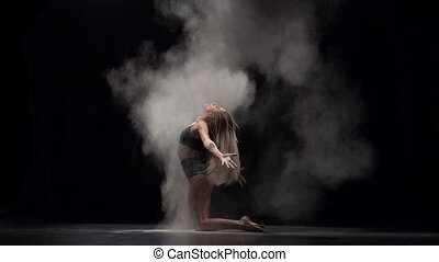 Slow motion of professional dancer throwing dust particles...