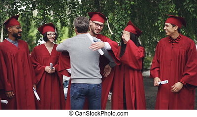 Slow motion of proud university teacher hugging his students and shaking hands, graduating students are standing in line with diplomas and laughing.
