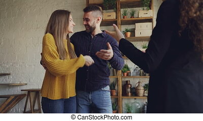 Slow motion of real estate buyers getting keys from cheerful housing agent after successful deal, kissing and hugging with happiness and shaking hands to female broker.