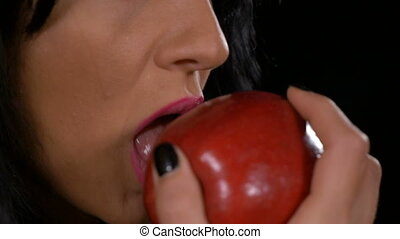 Slow motion of seductive woman biting a tasty red apple