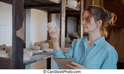 Slow motion of serious female potter checking ceramics and ...