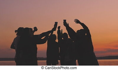 Slow motion of silhouette group young dancing people cheers and have a party at beach on sunset