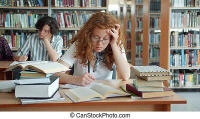 Slow motion of sleepy lady working in library then sleeping head on desk