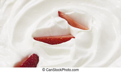 Slow motion of sliced strawberry falling into cream