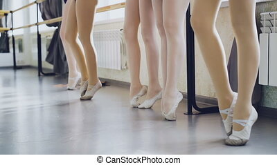 Slow motion of slim women's legs in pointe shoes standing on...