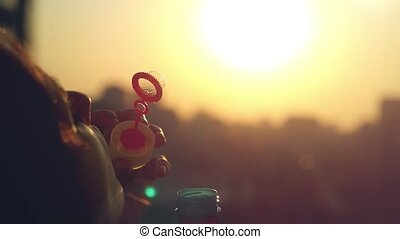 Slow motion of smiles young beautiful happy woman blowing bubble at sunset city
