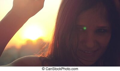 Slow motion of smiles young beautiful woman dancing and touching the sun  at sunset city