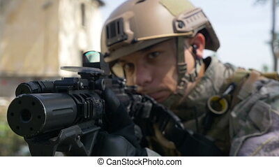 Slow motion of soldier with gun and headset aiming target in...