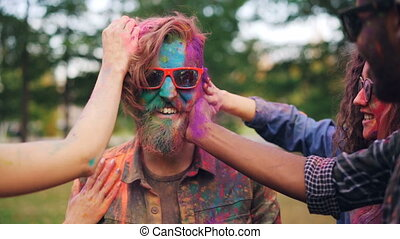 Slow motion of students dying bearded guy's face and hair with multicolor powder paint during Holi party outdoors, young man in sunglasses is laughing.