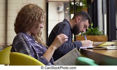 Slow motion of students prepare together for exams sitting in a cafe