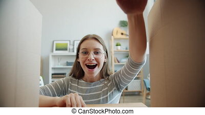 Slow motion of surprised girl opening box and looking inside expressing happiness and amusement positive emotions. Gifts, surprise and positivity concept.