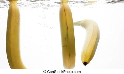 Slow motion of three fresh and ripe banas falling and...