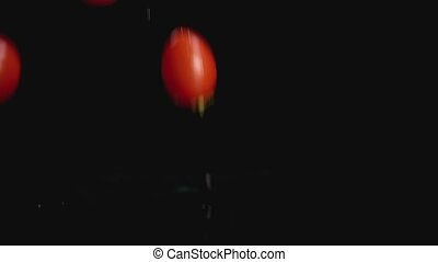 Slow motion of tomatoes falling in water on dark background with copy space
