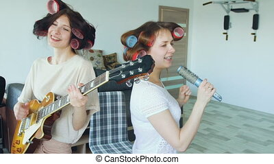 Slow motion of two funny girls singing with comb and playing electric guitar dance and sing