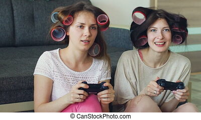 Slow motion of two funny women play console games with gamepad and have fun at home