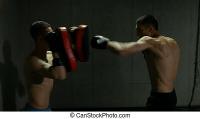 Slow motion of two male fighters training in gym studio with boxing gloves and thai pads
