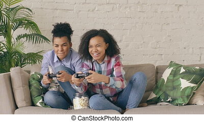 Slow motion of two mixed race curly girl friends sitting on couch play console computer games with gamepad and have fun at home