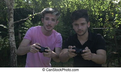 Slow motion of two young friends addicted to video gaming playing with controllers in a park outside