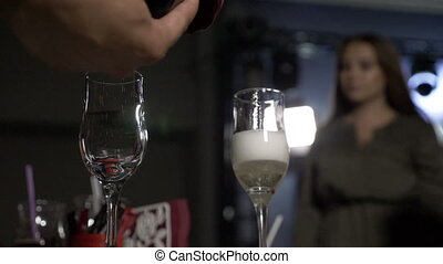 Slow motion of waiter pouring champagne in the glasses for happy girl