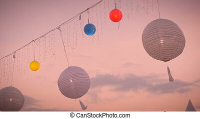Slow motion of white and colored lamp lanterns blowing in the wind at sunset