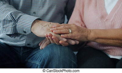 Slow motion of woman and man happy senior couple holding hands indoors