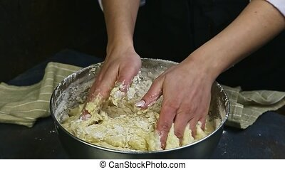 slow motion of woman by hands mix flour with liquid dough in...