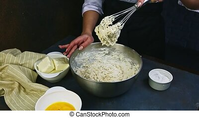 slow motion of woman holds in hand metal whisk with leftovers of soft dough falling into deep metal bowl stand on dark kitchen table