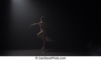 Slow motion of woman practicing contemp in dark studio under...