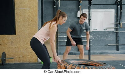 Slow motion of woman training in gym with rubber tyre lifting weight working out with trainer