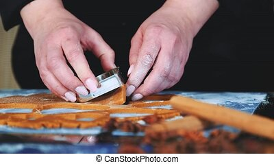 Slow motion of woman's hands using cookie cutter to make cookies. In front there are different spices.