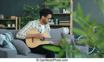 Slow motion of young Afro-American man playing the guitar singing song at home