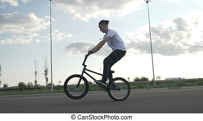 Slow motion of young biker pedaling and jumping practicing...