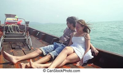Slow motion of young couple sitting at deck on drifting wooden boat enjoying their vacation. slwo motion. 1920x1080