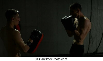 Slow motion of young fighters training in gym for kick boxing match using thai pads