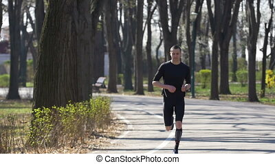 Slow motion of young fit sportive catching breath after jogging in the park