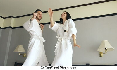 Slow motion of young happy couple in bathrobe jump and dance on bed in hotel during their honeymoon vacation