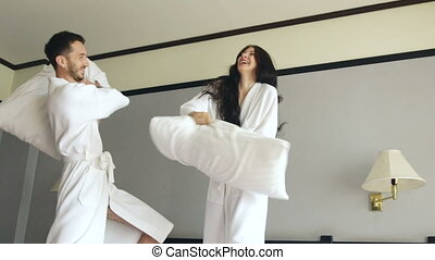 Slow motion of young happy couple in bathrobe fight pillows and have fun on bed in hotel during their honeymoon vacation