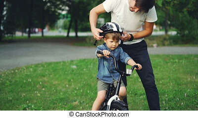 Slow motion of young man careful father holding bicycle helmet and talking to his son about safety then putting helmet on little boy's head and showing thumbs-up.