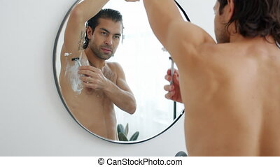 Slow motion of good-looking young man shaving armpit hair looking at mirror reflection in bathroom standing topless alone. People and depilation concept.