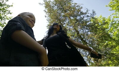 Slow motion of young mother singing and dancing with her little son spending quality time in park