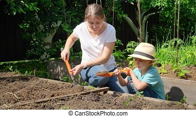 Slow motion video of young mother teaching her little son working at backyard garden and planting vegetables.