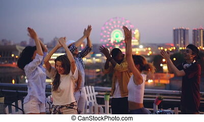 Slow motion of careless young people dancing and clapping hands at hight rooftop party with professional deejay. Men and women are having fun and relaxing at weekend.