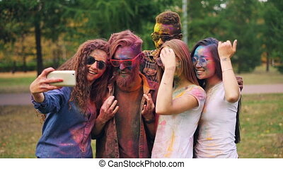 Slow motion of young people dirty with bright paint taking selfie in park using smartphone. Holi festival, modern technology and happy youth concept.