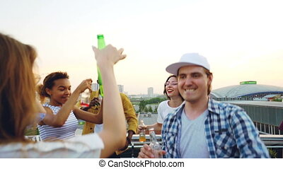 Slow motion of young people relaxing on rooftop with drinks dancing and clinking bottles celebrating holiday. Beautiful rooftop view of metropolis is in background.