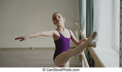 Slow motion of young slim ballerina practising alone at...