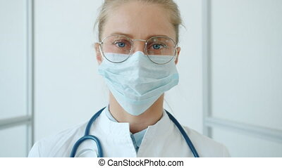 Slow motion of young woman doctor in swite suit and medical mask standing in clinic