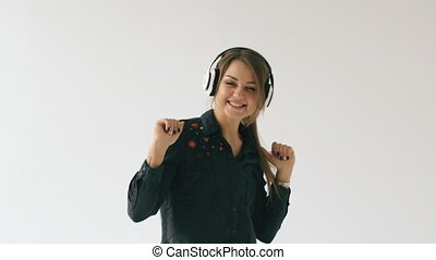 Slow motion of young woman in headphones listening music and dancing on white background indoors